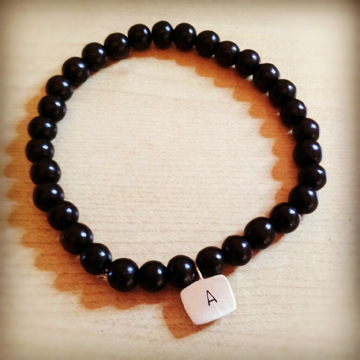 Hand stamped letter mala brown beaded bracelet (it's stretchy) ! Comes is 2 sizes men's & women's. You choose the size and pick the letter which I will hand stamp!  $25 Pledge.