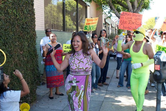 """Toxies co-emcee """"Consuelo Contaminación"""" greets """"Yellow Soap,"""" who crashed the ceremony with workers from the CLEAN Car Wash campaign in LA. Workers exposed to """"Yellow Soap"""" suffer acute health effects."""
