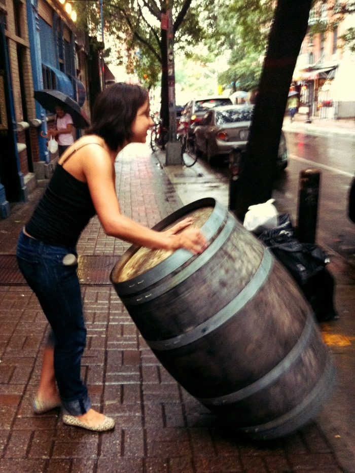 Brooke rolling a wine barrel down Clinton Street, to be used in the store.
