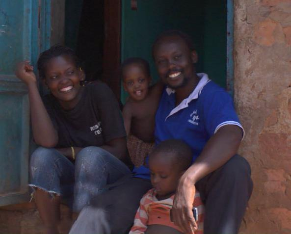 Filmmaker Isaac Nabwana with his family outside his home and studio in Wakaliga, Uganda