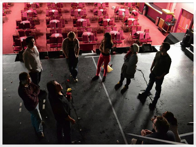 The actors are shown around the stage at the Pavilion.