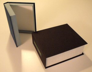 Two different archival clamshell boxes. Book cloth in two colors, one with spine label.