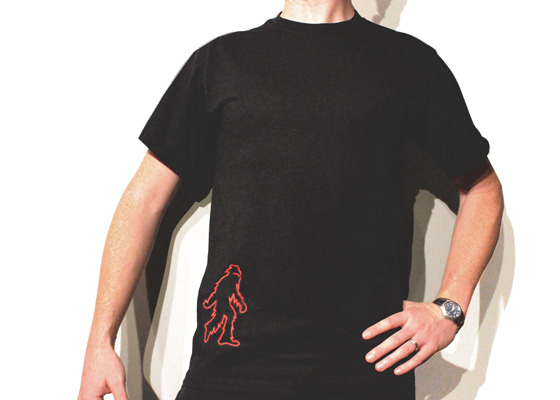 Sasquatch T-Shirt. Sizes: S,M,L,XL. Sizes are pretty standard (this image shows a Medium). Ladies' shirts include the heart on the Sasquatch. Men's do not include the heart.