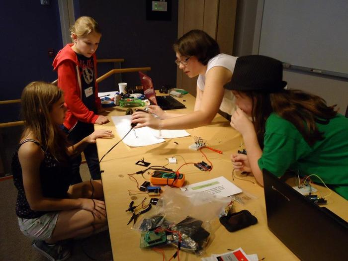 The team soldering their hardware.  Sarah -- ThoughtSTEM Co-Founder -- explains how it's done.