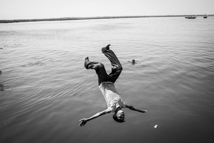 A boy flips into the water after jumping from a dock in Rehri Goth
