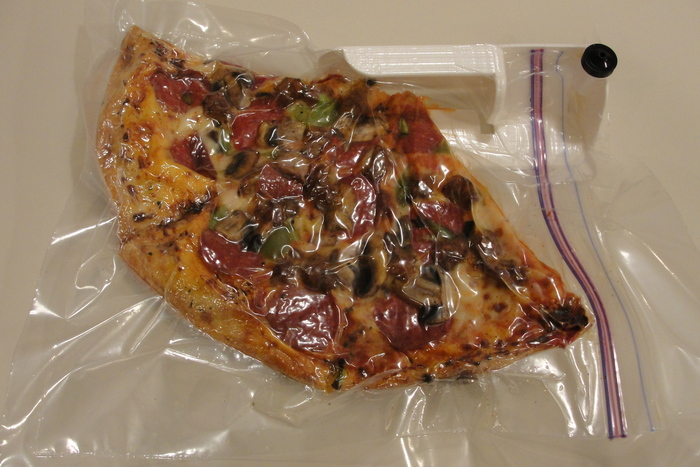 Leftover large pizza vacuum packed in a gallon-size food bag.