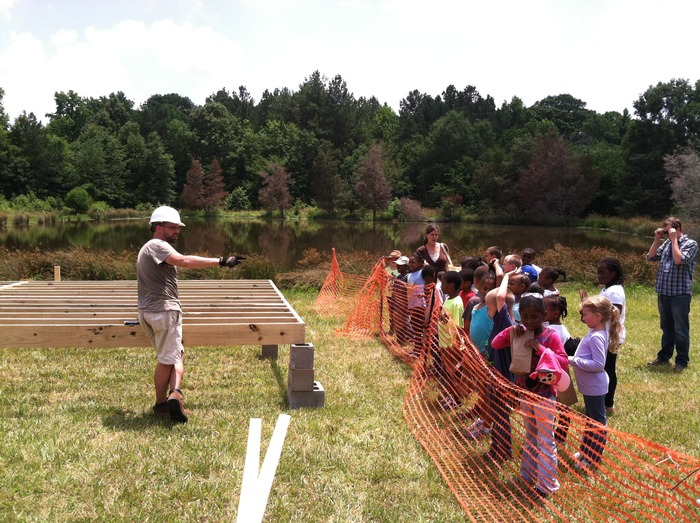 Adam, NCSU graduate student, showing DPS Summer Camp kids the framework for the Floating Lab.