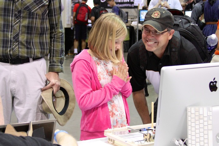 A young visitor plays with the WaterColorBot at Maker Faire