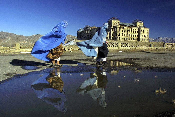 Afghan women walk in front of the Darulaman Palace in Kabul, on a breezy winter day.