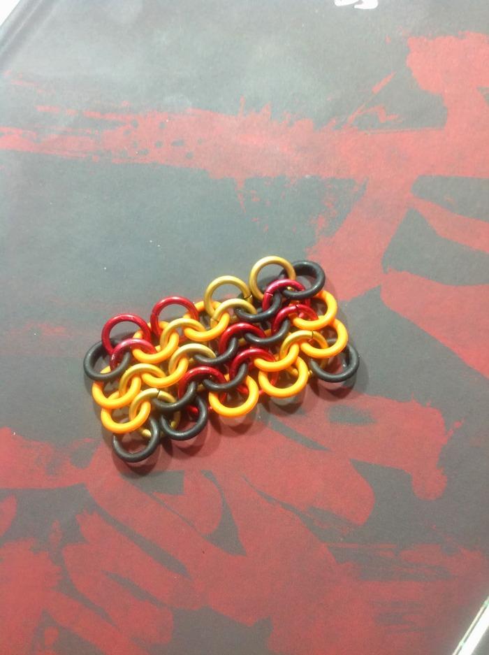 Double Spiral - Red / Gold Metal + Orange / Black Rubber