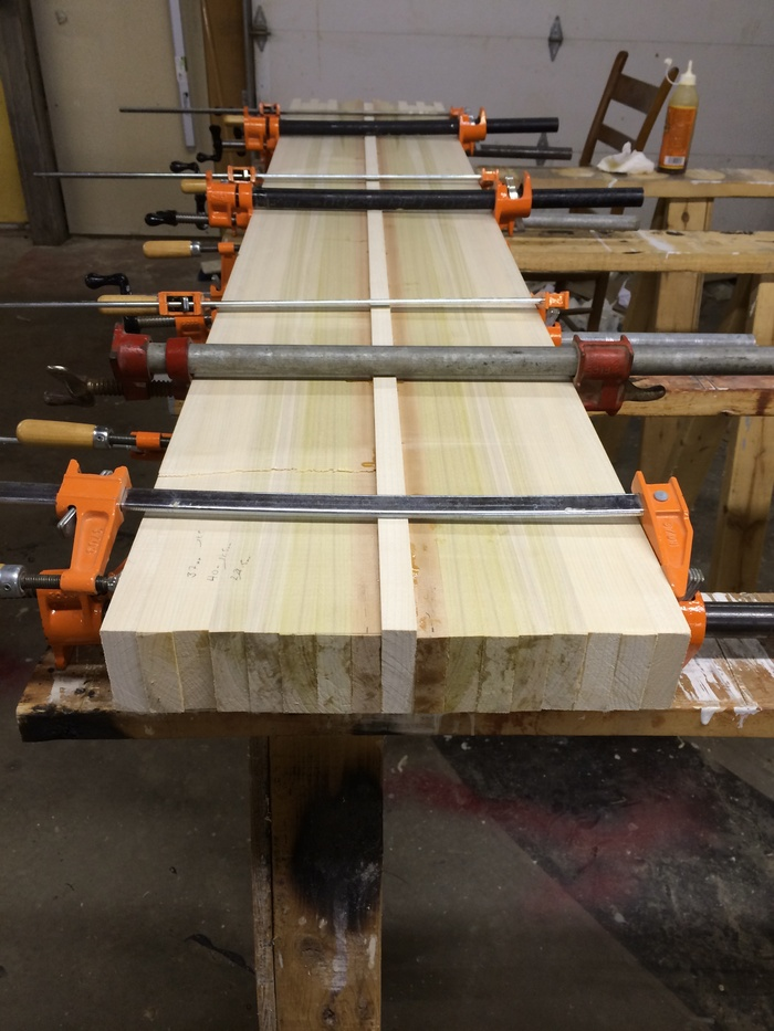 A core block made up of vertically laminated Poplar and Birch dries in a set of clamps.